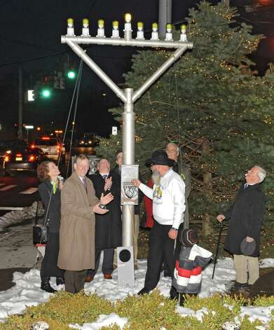 Rabbi Nachman Simon, third from right, lights the menorah for Bethlehem Chabad's third annual Hanukkah celebration in the Four Corners on Tuesday, Dec. 16, 2014 in Delmar, N.Y. (Lori Van Buren / Times Union) Photo: Lori Van Buren / 00029733A