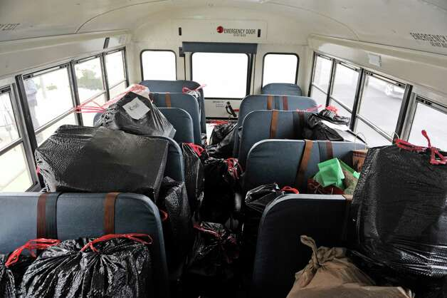 Bags full of children's gifts are seen on a bus at Christian Brothers Academy after students loaded the bus outside the school on Tuesday, Dec. 16, 2014, in Colonie, N.Y.  For ten years the students in the National Honor Society and the Junior Honor Society have organized the Adopt-A-Family Program at the school.  Students, parents, faculty and staff all take part in the program where children's gifts are purchased and wrapped.  The gifts, for children ranging in age from newborn to 13 years old, are delivered to an Albany public school and distributed to parents in the program.  Thirty-six children from 17 families will receive gifts through the program this year.   (Paul Buckowski / Times Union) Photo: Paul Buckowski / 00029868A