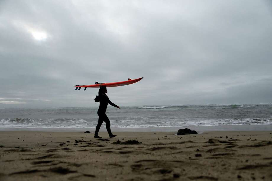 Bianca Valenti carries her surfboard on Maverick Beach before surfing in Half Moon Bay, Calif., on Tuesday, December 9, 2014. Photo: Scott Strazzante / The Chronicle / ONLINE_YES