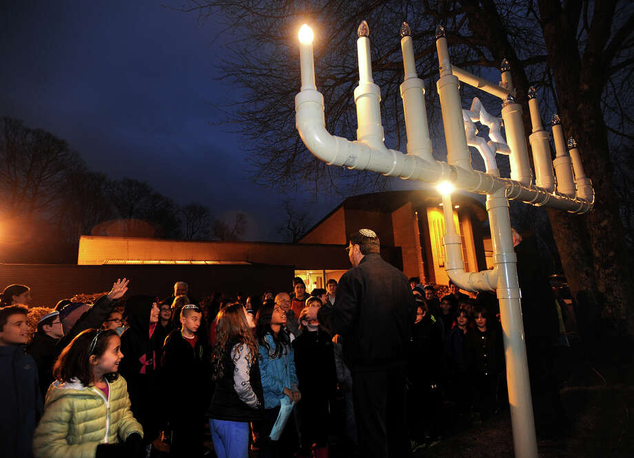 Rabbi Colin Brody, left, and Manny Lobel, of Trumbull,  conduct the menorah lighting ceremony for Hebrew school children for the first night of Hannukkah outside Congregation B'nai Torah on Main Street in Trumbull, Conn. on Tuesday, December 16, 2014. Lobel, an engineer by trade, constructed the menorah in 1978. Photo: Brian A. Pounds / Connecticut Post