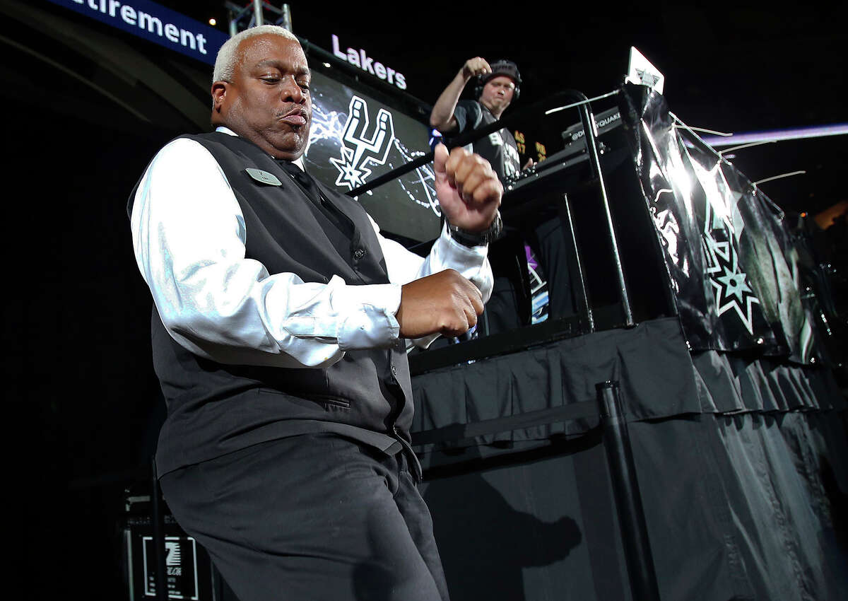 Eric Byrd, an Our Lady of the Lake employee, performs as the dancing usher with DJ Quake (David Gamez) in the background at the Spurs game against the Lakers at the AT&T Center on December 12, 2014.