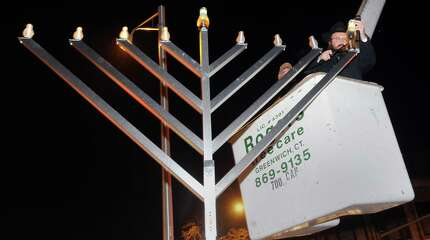 Rabbi Yossi Deren of the Chabad of Greenwich lights the giant Menorah from the basket of a utility truck during the first night of Hanukkah that was celebrated at the YMCA of Greenwich, Conn., Tuesday night, Dec. 16, 2014.