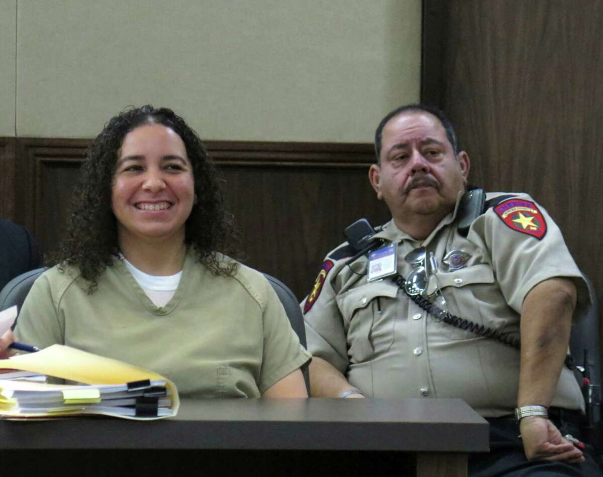 Hannah Overton, who was convicted in 2007 in the death of a child and recently had her conviction overturned by the Texas Court of Criminal Appeals, smiles during her bail hearing as she sits by a bailiff in Corpus Christi on Tuesday, Dec. 16, 2014. Overton was granted bail.