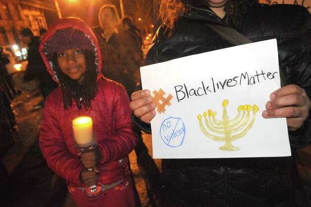 Ten-year-old Haleliya Wilson, left, and her mother Stefanie Wilson both of Saratoga Springs and with Temple Sinai take part in the Albany chapter of Jewish Voices for Peace rally at Dana Park on Tuesday Dec. 16, 2014 in Albany ,N.Y. The group is held the event on the first night of Hanukkah to draw parallels over public anger over police killing unarmed blacks people and a holiday based on a small band of Jews who overcame oppressors. (Michael P. Farrell/Times Union) Photo: Michael P. Farrell / 00029877A