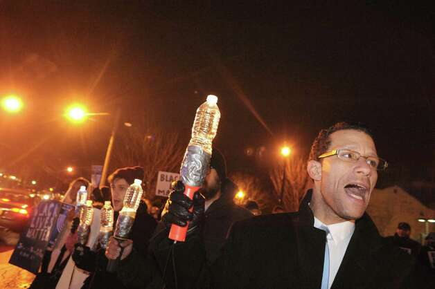 Andres Rivera, right, takes part in the Albany chapter of Jewish Voices for Peace rally at Dana Park on Tuesday Dec. 16, 2014 in Albany ,N.Y. The group is held the event on the first night of Hanukkah to draw parallels over public anger over police killing unarmed blacks people and a holiday based on a small band of Jews who overcame oppressors. (Michael P. Farrell/Times Union) Photo: Michael P. Farrell / 00029877A