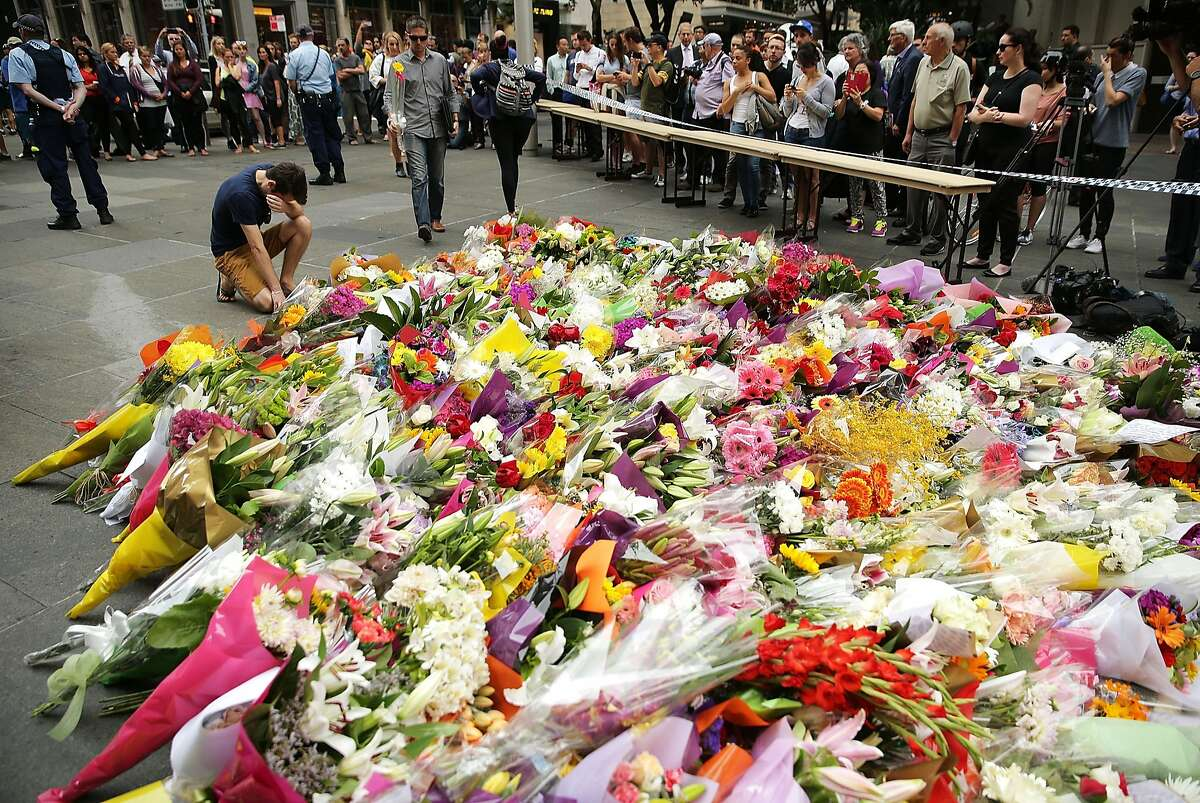 SYDNEY, AUSTRALIA - DECEMBER 16: A man cries as he pays his respect at Martin Place on December 16, 2014 in Sydney, Australia. The siege in Sydney's Lindt Cafe in Martin Place is over after 16 hours. Police raided the cafe just after 2am AEDT on Tuesday morning. Three people have been confirmed killed, two hostages and the gunman. (Photo by Mark Metcalfe/Getty Images) *** BESTPIX ***