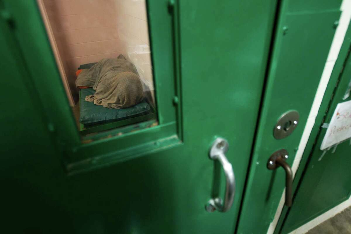 An incarcerated female inmate lies covered in a blanket in a cell in one of the mental health pods at the Harris County Jail Wednesday, April 13, 2011, in Houston. ( Brett Coomer / Houston Chronicle )