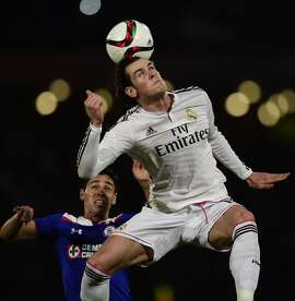 Real Madrid's Gareth Bale heads the ball away from Cruz Azul's Fausto Pinto during a FIFA World Club Cup semifinal.