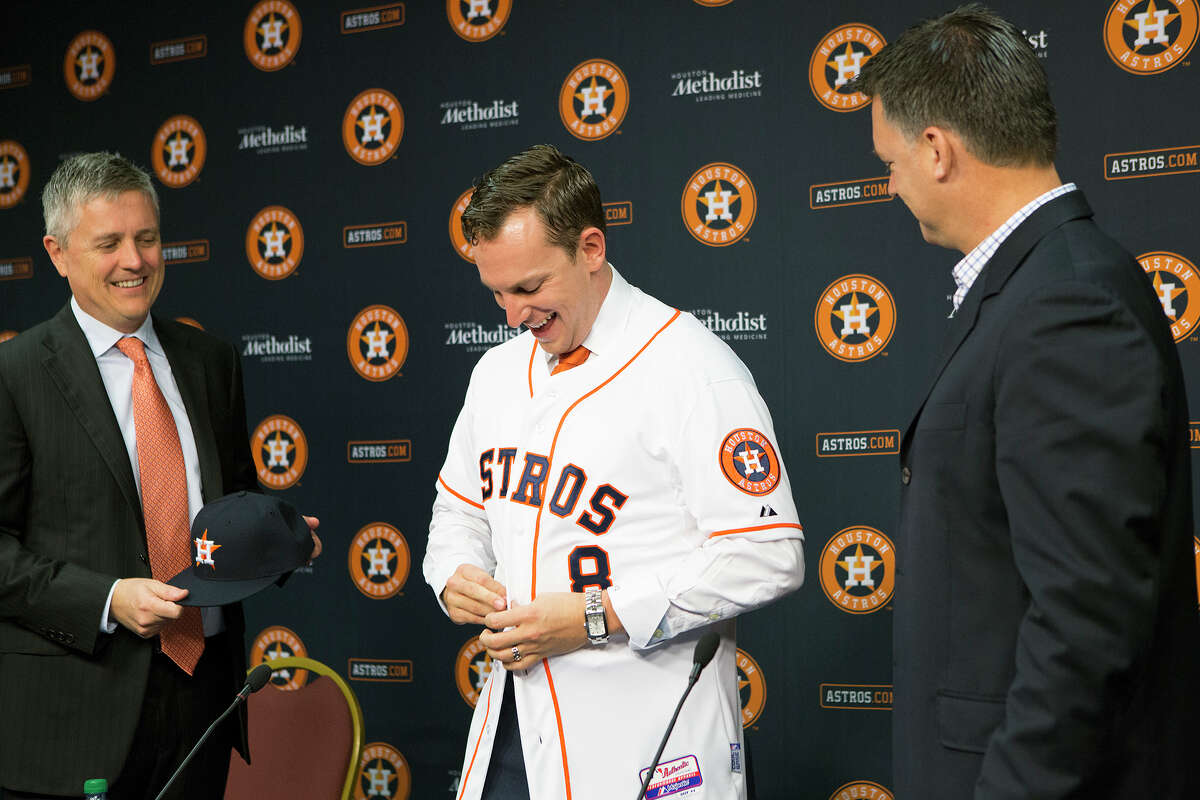 General Manager Jeff Luhnow, left, and Astros Coach, A.J. Hinch, right, welcome back free-agent shortstop Jed Lowrie during a news conference at Minute Maid Park, Tuesday, Dec. 16, 2014, in Houston. (Cody Duty / Houston Chronicle)