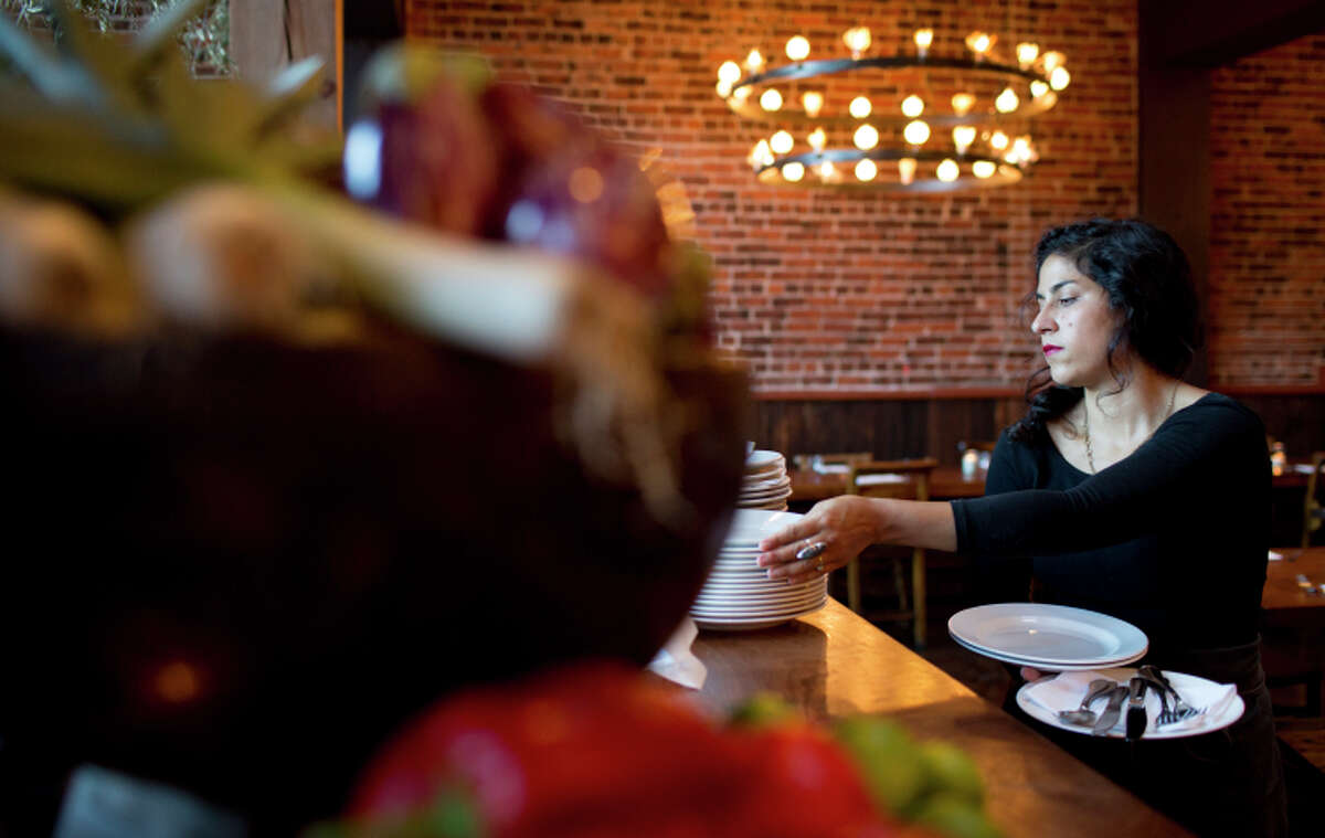 Rose DeStefano grabs plates at Oakland's Camino, one of several restaurants to eliminate tipping.