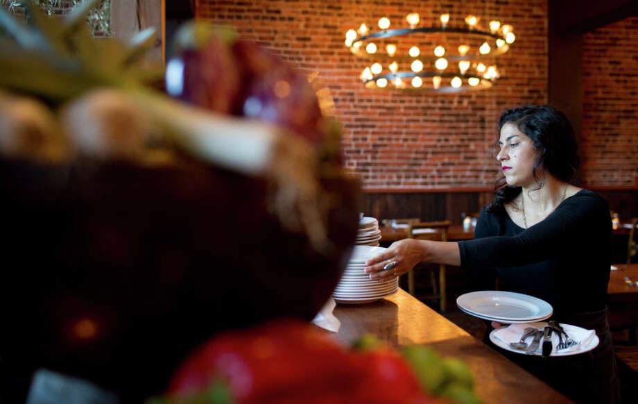 Rose DeStefano grabs plates at Oakland's Camino, one of several restaurants to eliminate tipping. Photo: Tim Hussin / Special To The Chronicle / ONLINE_YES