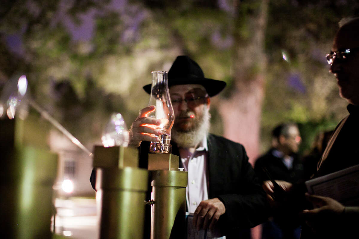 Rabbi Chaim Block covers the flame after lighting a menorah, made by Mark Greenwald fifteen years ago, Tuesday Dec. 16, 2014 in front of Shavano Park's city hall during the lighting Hanukkah ceremony by members of the Jewish community. This is the first celebration of it's kind, and the menorah will be lit every night until the final night on Wednesday Dec. 24.