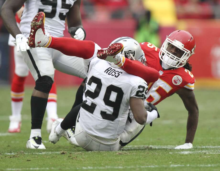 Kansas City Chiefs running back Jamaal Charles (25) is tackled by Oakland Raiders strong safety Brandian Ross (29) during the first half of an NFL football game in Kansas City, Mo., Sunday, Dec. 14, 2014. (AP Photo/Ed Zurga)