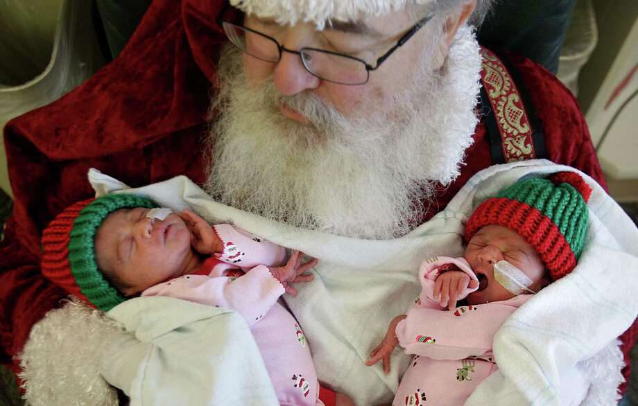 Jolly St. Nick gently holds newborn twins, Alexa Ochoa and Camila Ochoa while getting ready for baby's first santa photos in the Neonatal Intensive Care Unit at Memorial Hermann Southwest on Tuesday, Dec. 16, 2014, in Houston. Photo: Mayra Beltran, Houston Chronicle / © 2014 Houston Chronicle