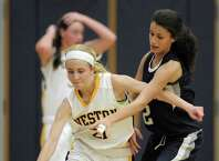 Weston's Taylor Kennedy (21) tries to dribble around Immaculate's Stephanie Bischop (2) during the SWC girls high school basketball game between Immaculate and Weston high schools, on Tuesday night, December 16, 2014, played at WestonHigh School, Weston, Conn.