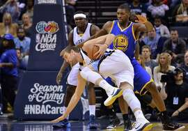 Memphis Grizzlies center Marc Gasol struggles to stay on his feet against Golden State Warriors center Festus Ezeli (31) in the first half of an NBA basketball game Tuesday, Dec. 16, 2014, in Memphis, Tenn. (AP Photo/Brandon Dill)