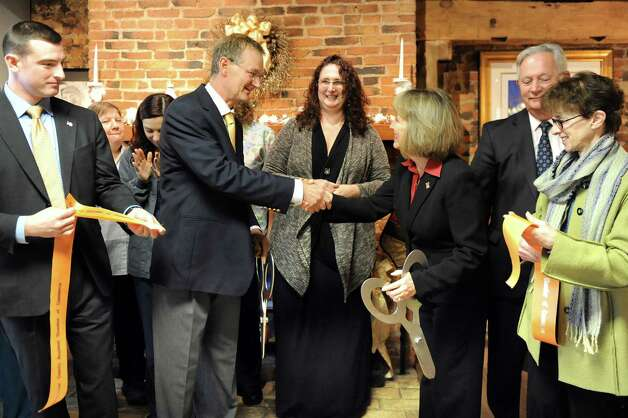 Veterinarian Kimberly Linendoll, center, and husband Tim Ballard, second from left, receive congratulations from Rensselaer County Executive Kathy Jimino, third from right following a ribbon cutting on Tuesday Dec. 16, 2014, at the Collar City Animal Hospital in Troy, N.Y. Joining them are, from left, City Councilman Jim Gordon, Deputy Mayor Pete Ryan and City Councilwoman Lynn Kopka. The clinic will host an open house for the public on Saturday from 11 a.m. to 3 p.m. (Cindy Schultz / Times Union) Photo: Cindy Schultz / 00029872A