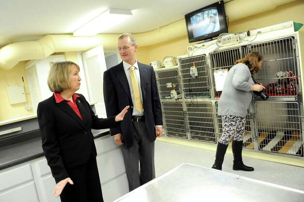 Rensselaer County Executive Kathy Jimino, left, takes a tour with Tim Ballard, general contractor and husband to veterinarian Kimberly Linendoll (not pictured) on Tuesday Dec. 16, 2014, at the Collar City Animal Hospital in Troy, N.Y. At right, family member Patty Miller peeks in on a patient. (Cindy Schultz / Times Union) Photo: Cindy Schultz / 00029872A