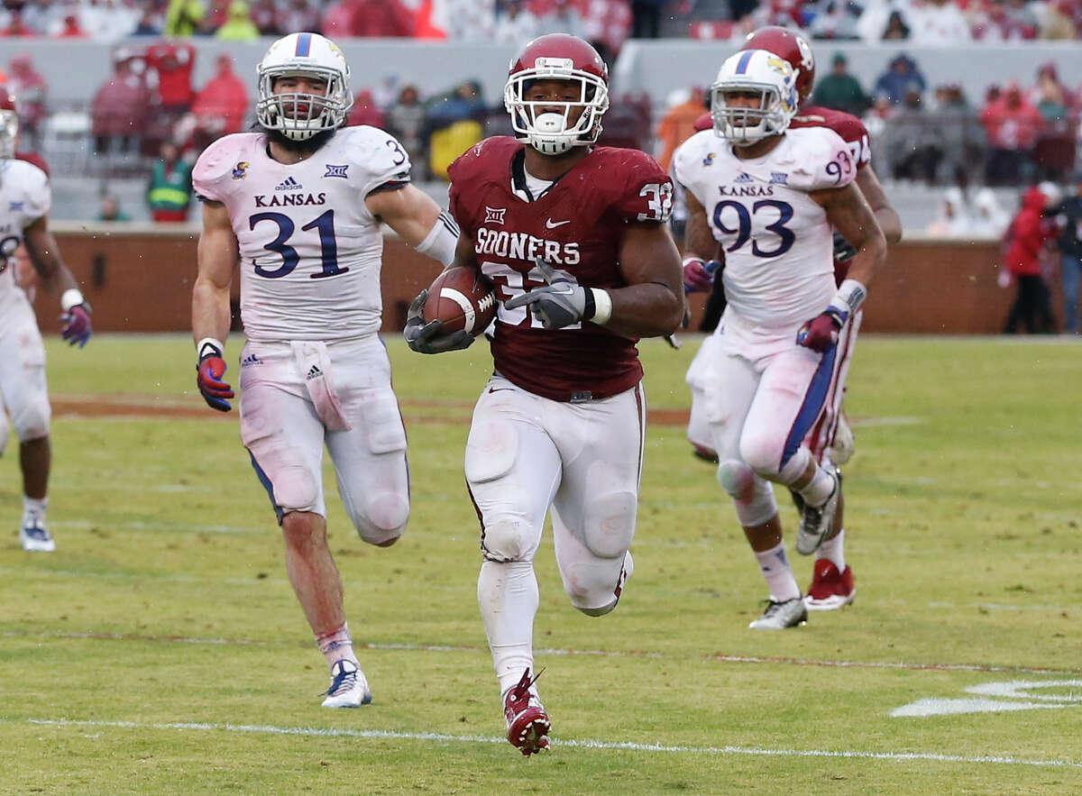 Oklahoma's Samaje Perine sprints towards the end zone on a touchdown run ahead of Kansas' Ben Heeney (31) and Ben Goodman (93) during the second quarter in Norman, Okla., on Nov. 22.