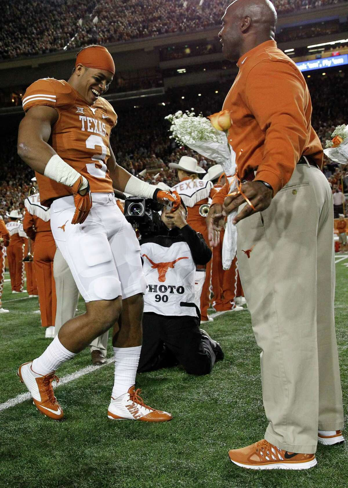Jordan Hicks #3 of the Texas Longhorns is introduced and meets head coach Charlie Strong as the seniors were honored before playing the TCU Horned Frogs at the Darrell K Royal -Texas Memorial Stadium on November 27, 2014 in Austin. Texas. (Photo by Chris Covatta/Getty Images)