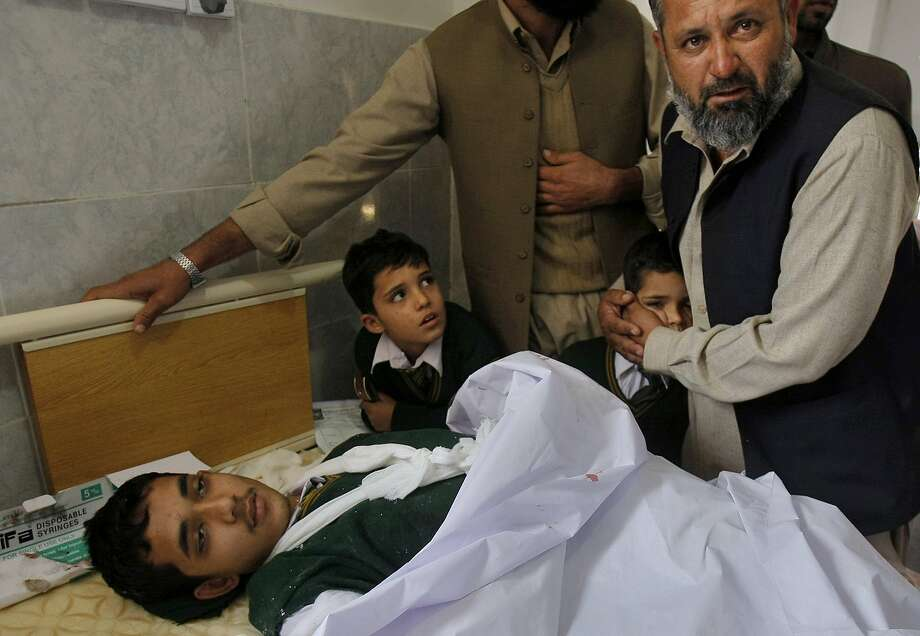 A Pakistani man comforts a student standing at the bedside of a boy who was injured in a Taliban attack on a school, at a local hospital in Peshawar, Pakistan, Tuesday, Dec. 16, 2014. Taliban gunmen stormed a military-run school in the northwestern Pakistani city of Peshawar on Tuesday, killing and wounding scores, officials said, in the worst attack to hit the country in over a year.(AP Photo/Mohammad Sajjad) Photo: Mohammad Sajjad, Associated Press
