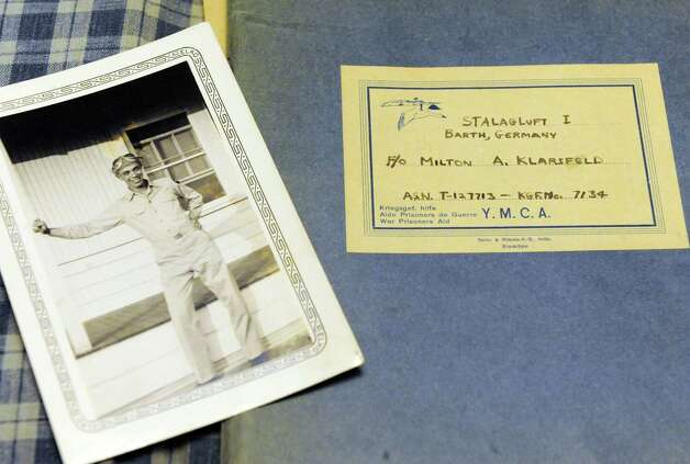 A photo from 1943 of World War II veteran Milton Klarsfeld and the cover of a diary he kept as a POW on Thursday Dec. 11, 2014 in Slingerlands, N.Y. Klarsfeld is now 92 and the last surviving member of Arsenic & Lace, a B24 that was eventually shot down on December 17, 1944, over Olomouc in what is now the Czech Republic. The mission originated from Italy. He was taken POW until end of the war.  (Michael P. Farrell/Times Union) Photo: Michael P. Farrell / 00029822A