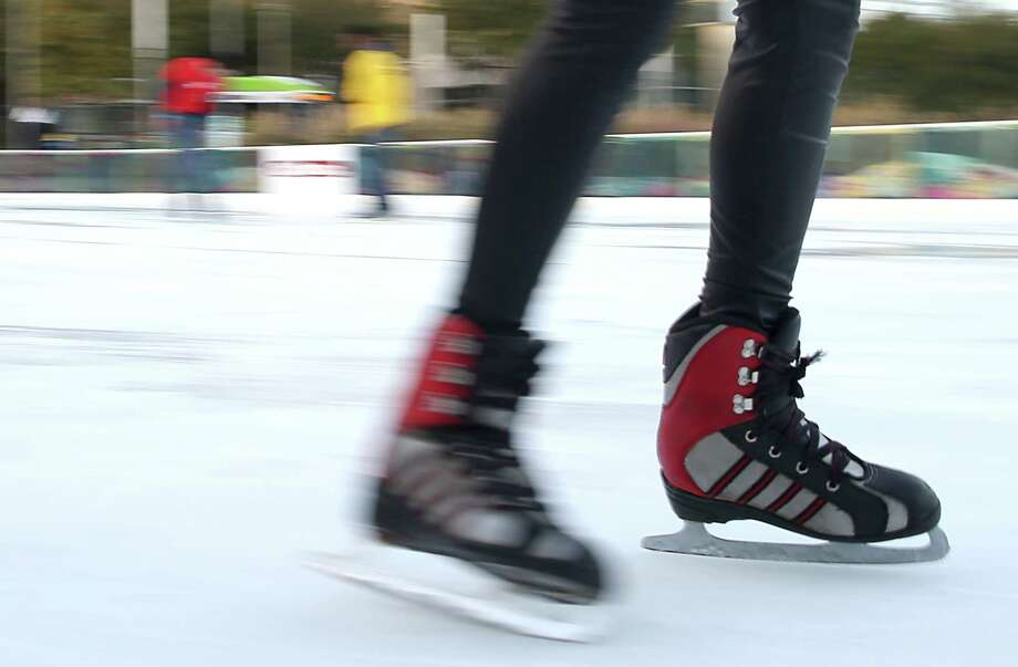 Adults and children skate around Discovery Green Ice Rink on Tuesday, December 9, 2014 in Houston, TX.  A slow camera shutter speed freezes still subjects while bluring those in motion. (Photo: Thomas B. Shea/For the Chronicle) Photo: Thomas B. Shea / © 2014 Thomas B. Shea