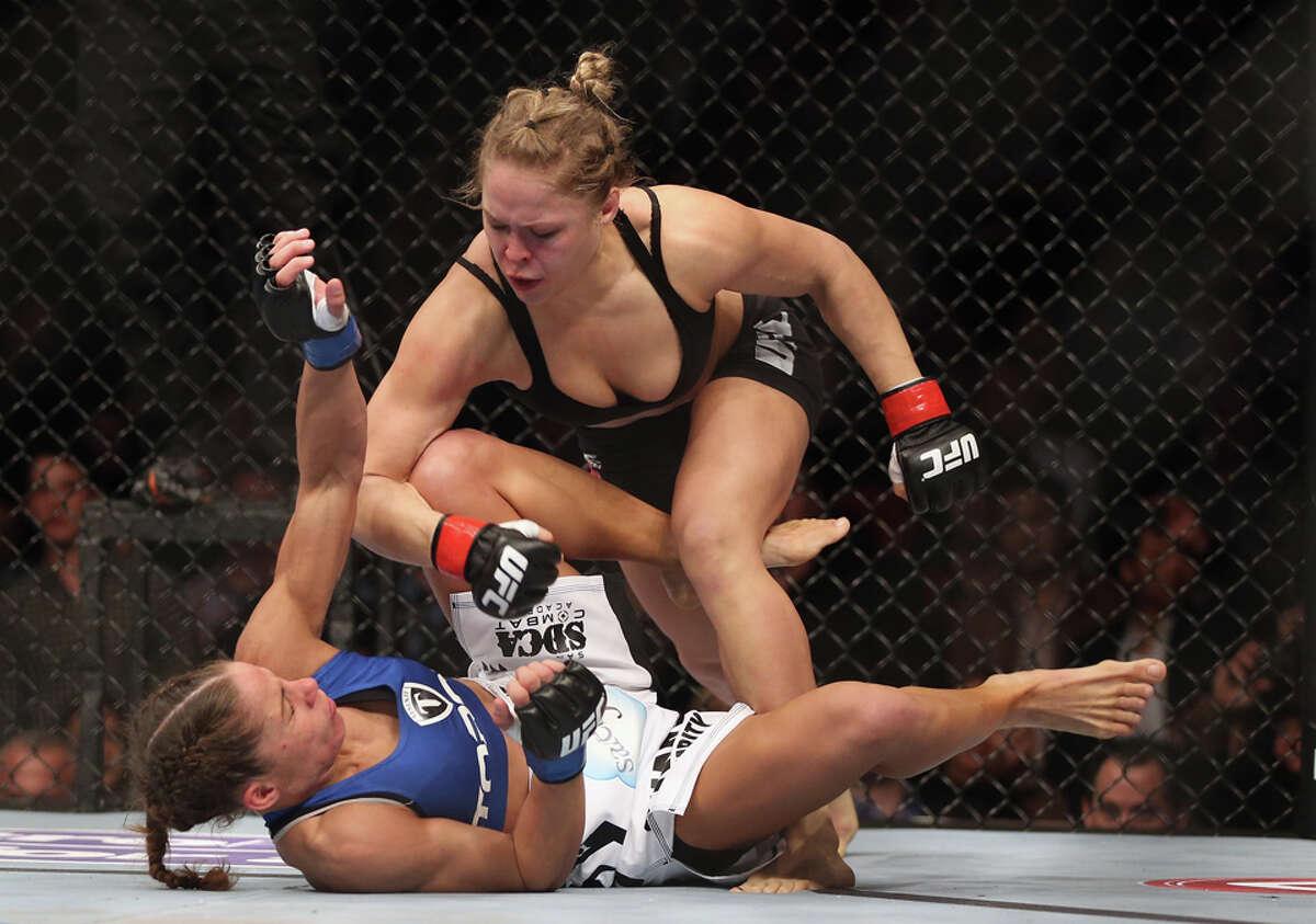 ANAHEIM, CA - FEBRUARY 23: Ronda Rousey hits Liz Carmouche during their UFC Bantamweight Title fight at Honda Center on February 23, 2013 in Anaheim, California.