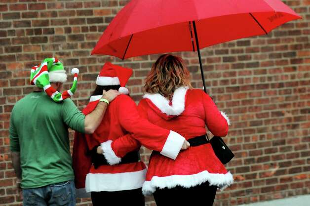 Revelers protect themselves from the rain as they leave the Putnam Den for the Parting Glass during SantaCon on Saturday, Dec. 21, 2013, in Saratoga Springs, N.Y. The pub crawl aims to collect canned goods for the Franklin Community Center food pantry. (Cindy Schultz / Times Union) Photo: Cindy Schultz / 00025127A
