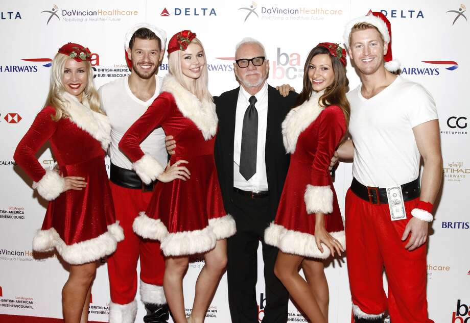 A couple of barely-clad Santas and their helpers hang out with actor Malcolm McDowell.