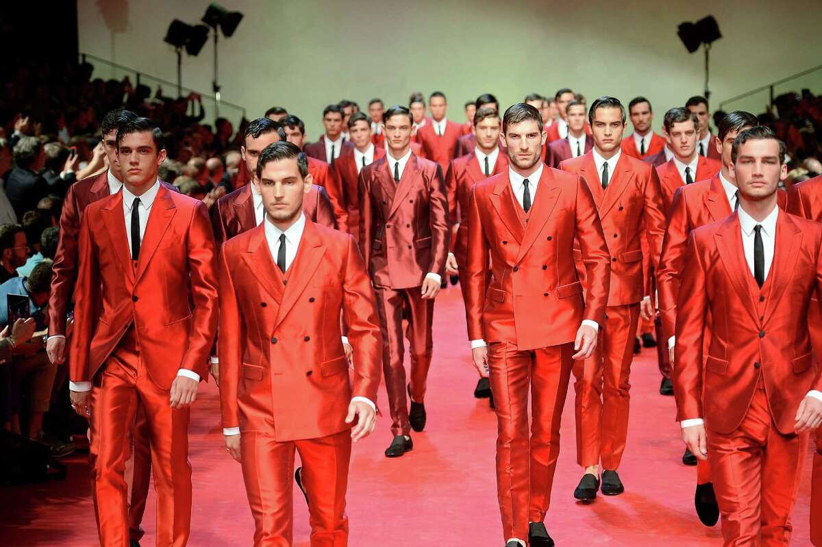 Wearing red can be a risky color for guys, but designers worked the hot hue into their collections for spring. Here, an army of red Dolce & Gabbana shiny suits.