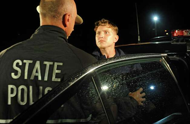 Shane Harding stares down an officer before putting up a struggle as the police put him in the state police car after his arraignment at North Greenbush Town Court on Wednesday, Oct. 1, 2014 in Wynantskill, N.Y.  (Lori Van Buren / Times Union archive) Photo: Lori Van Buren / 00028864A