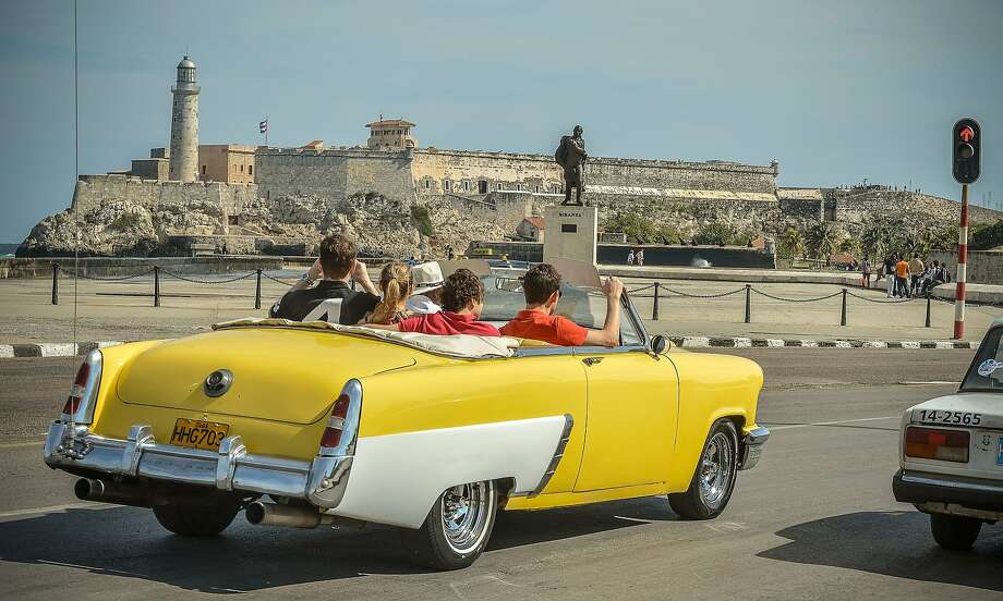 Tourists take a ride in a fully restored Mercury along the coast in Havana on March 18, 2013. Photo: Adalberto Roque