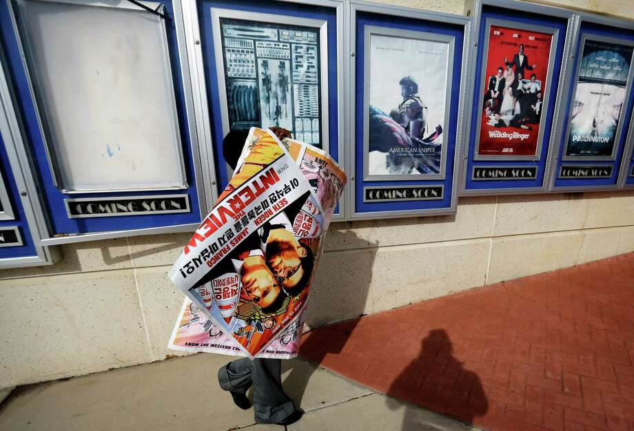 """A poster for the movie """"The Interview"""" is carried away by a worker after being pulled from a display case at a Carmike Cinemas movie theater, Wednesday, Dec. 17, 2014, in Atlanta. Georgia-based Carmike Cinemas has decided to cancel its planned showings of """"The Interview"""" in the wake of threats against theatergoers by the Sony hackers. (AP Photo/David Goldman) Photo: David Goldman, Associated Press / AP"""