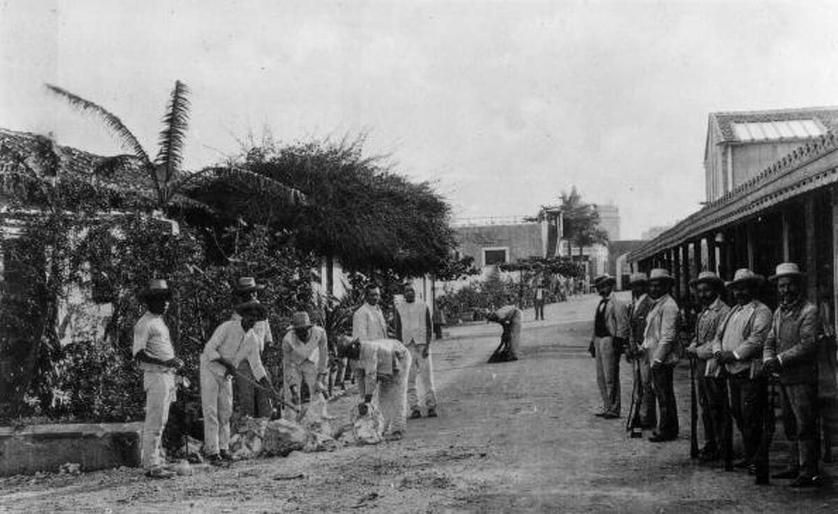 Life in Cuba before the trade embargo A circa-1890 photo of prisoners breaking stones the grounds of Presidio Infirmary under the watchful eye of several armed men in Havana, Cuba.
