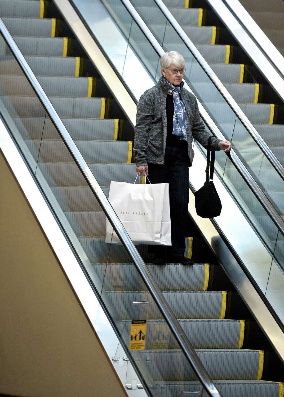 Pat Cooney, of Danbury, rides the escalator while shopping in the Danbury Fair Mall, on Wednesday, December 17, 2014.