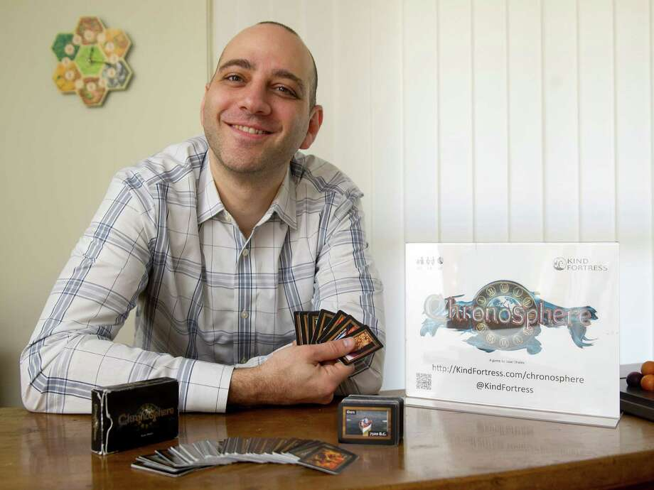 Isaac Shalev poses for a photo with the card game he designed, ChronoSphere, in his Stamford home on Wednesday, December 17, 2014. Photo: Lindsay Perry / Stamford Advocate