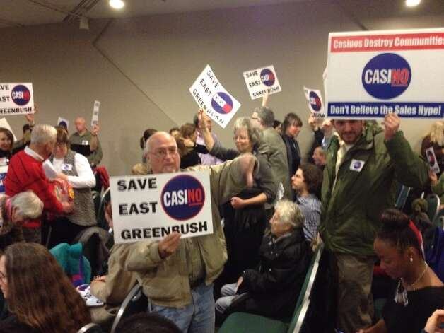 Opponents of an East Greenbush casino hold placards as they await the state's decision on casino sites. (John Carl D'Annibale / Times Union)