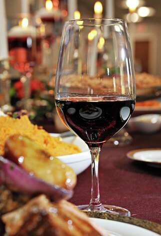 A glass of pinot noir on a holiday table at Mazzone Hospitality Corporate Headquarters Wednesday Nov. 12, 2014, in Clifton Park, NY.  (John Carl D'Annibale / Times Union) Photo: John Carl D'Annibale / 00029449A