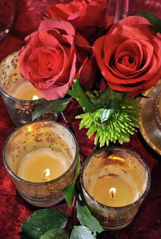 Votive candles and roses on a holiday table at Mazzone Hospitality Corporate Headquarters Wednesday Nov. 12, 2014, in Clifton Park, NY.  (John Carl D'Annibale / Times Union) Photo: John Carl D'Annibale / 00029449A
