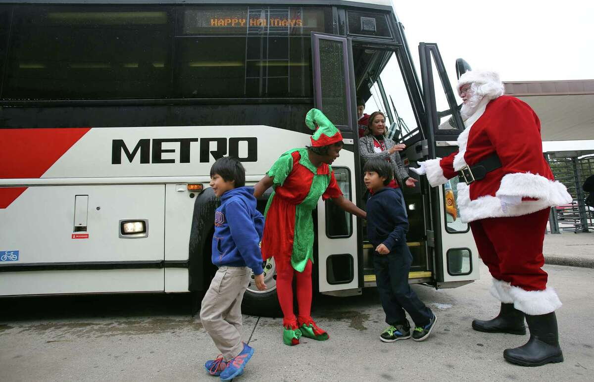 Metro employee Sheila Showers and Metro bus driver Charles Richmond escort children from the bus on way to their annual holiday party for low-income children at Metro's Fallbrook facility on Wednesday, Dec. 17, 2014, in Houston.