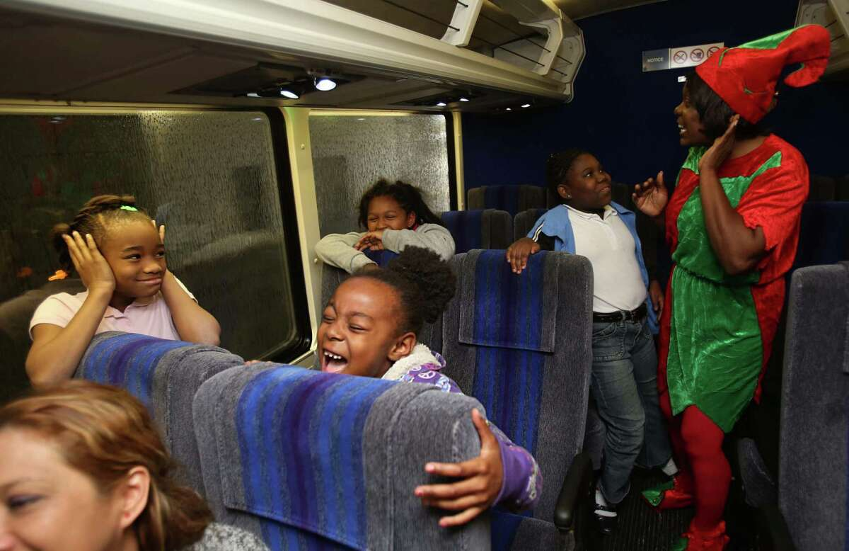 Allure Smith and Arieanna Bishop scream while the Metro bus drivers drives a bus through the carwash to kick off their annual holiday party for low-income children at Metro's Fallbrook facility on Wednesday, Dec. 17, 2014, in Houston.