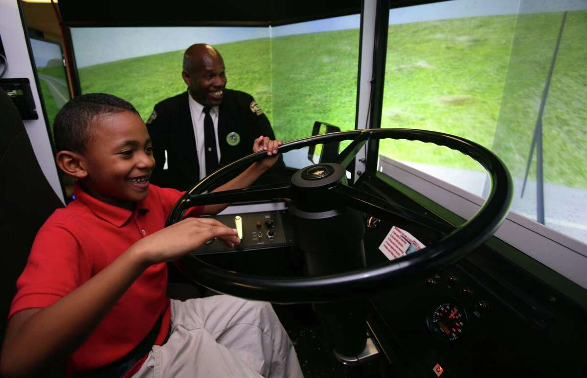 Tristen Davis plays with the bus simulator while instructor Reginald Wilmore supervises during Metro's annual holiday party for low-income children at Metro's Fallbrook facility on Wednesday, Dec. 17, 2014, in Houston.