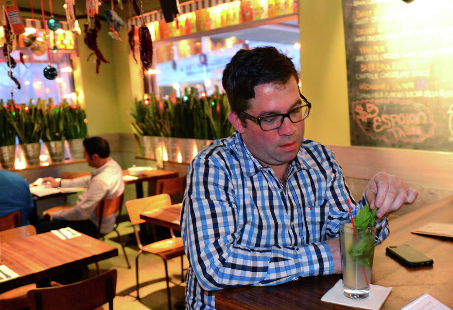 Michael Young, who was trained by prominent Cuban chef Douglas Rodriguez, said he hopes the thawing of US relations with Cuba will lead to a cultural exchange.  Young owner of the Mexican restaurant Bodega Taco Bar, comments on the news about Cuba while he sits at the bar with a mojito at the restaurant in Fairfield, Conn., on Wednesday Dec. 17, 2014. Photo: Christian Abraham / Connecticut Post