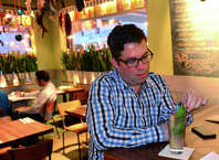 Michael Young, who was trained by prominent Cuban chef Douglas Rodriguez, said he hopes the thawing of US relations with Cuba will lead to a cultural exchange.  Young owner of the Mexican restaurant Bodega Taco Bar, comments on the news about Cuba while he sits at the bar with a mojito at the restaurant in Fairfield, Conn., on Wednesday Dec. 17, 2014.