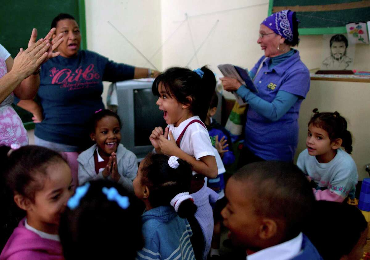 Students and teachers at a school in Havana celebrate as they listen to the live broadcast of a speech by Cuban President Raul Castro telling the island nation's people about the restoration of political and economic relations with the United States. ,