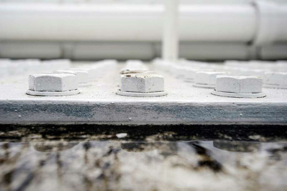 A puddle of water sits next to bolts on top of the Eastern span of the Bay Bridge in Oakland, CA Monday, February 10, 2014. Photo: Michael Short / Special To The Chronicle / ONLINE_YES
