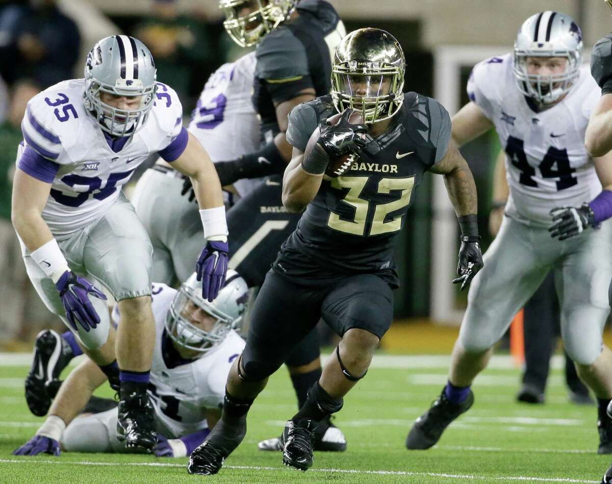 Baylor running back Shock Linwood breaks through the line Kansas State linebacker Will Davis (left) and defensive end Ryan Mueller (right) give chase.