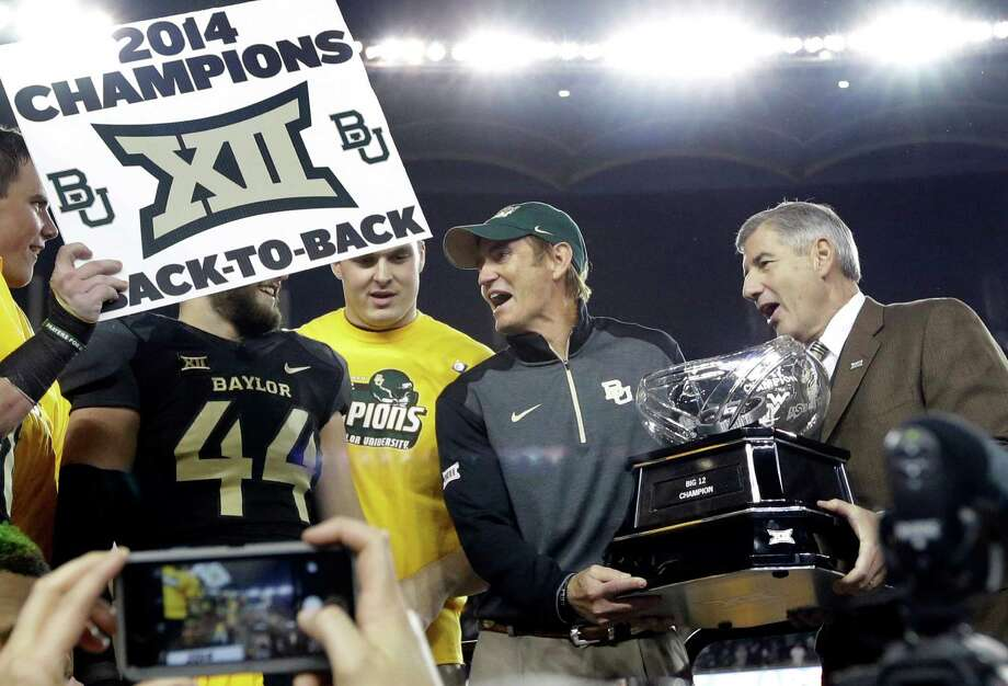 Big 12 Commissioner Bob Bowlsby, right, presents Baylor head coach Art Briles, center, with the conference trophy after their 38-27 win over Kansas State in an NCAA college football game, Saturday, Dec. 6, 2014, in Waco, Texas. (AP Photo/Tony Gutierrez) Photo: Tony Gutierrez, STF / Associated Press / AP