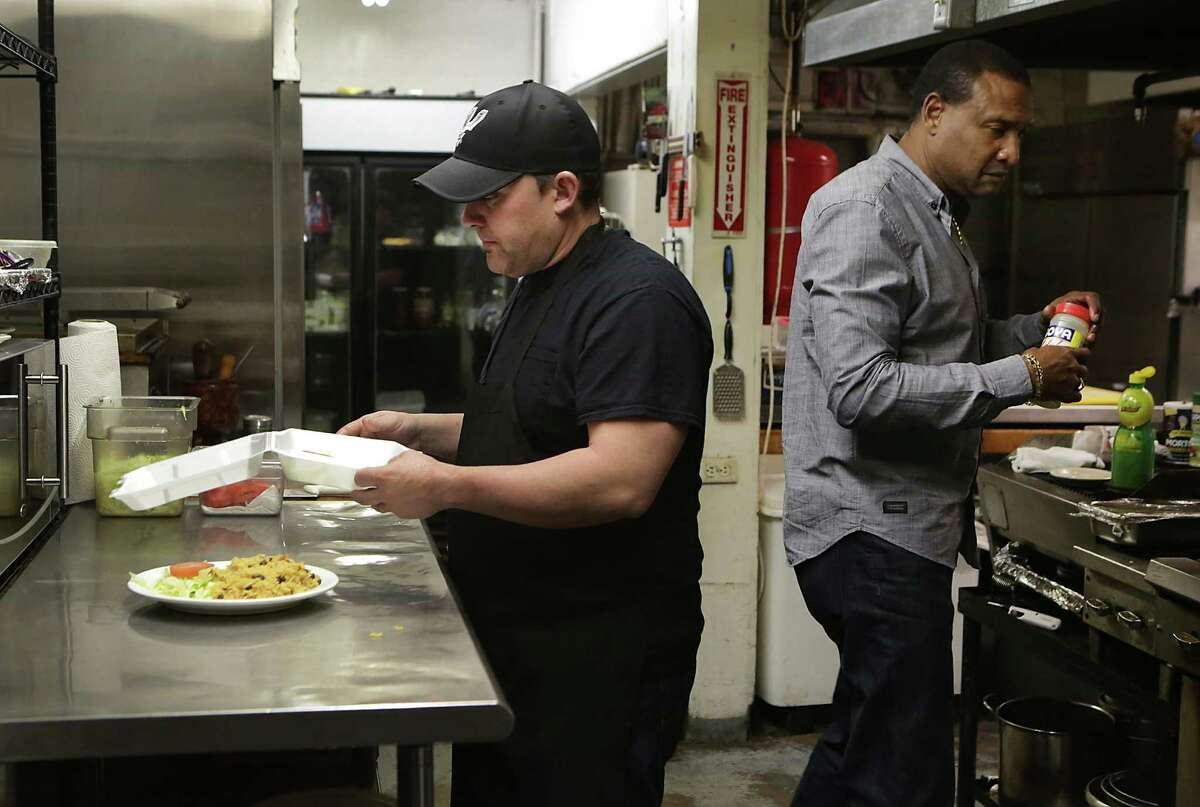 Oscar Sori, left, 36, who arrived recently in the U.S. from Cuba, now a cook at El Bohio Restaurant, works in the kitchen with restaurant owner Andres Serbones, right. Wednesday, Dec. 17, 2014.